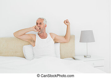 Mature man stretching his arms in bed - Mature man waking up...