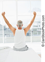 Rear view of mature man stretching arms in bed