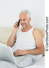 Mature man using cellphone and laptop in bed - Casual...