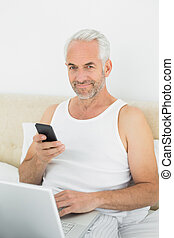 Smiling mature man with cellphone a - Portrait of a casual...