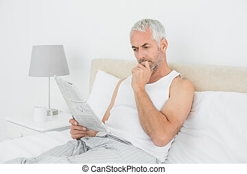 Mature man reading newspaper in bed at home