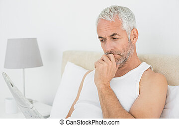 Mature man reading newspaper in bed