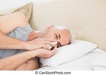 Close-up of a mature man suffering from cold in bed -...