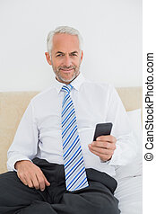 Smiling well dressed man text messaging in bed - Portrait of...