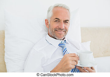 Smiling businessman with a cup of tea in bed - Portrait of a...