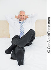 Portrait of a relaxed mature businessman sitting in bed -...