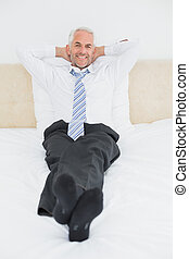 Relaxed mature businessman sitting in bed - Full length...