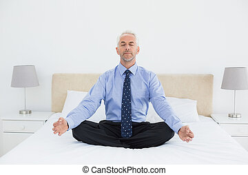 Relaxed mature businessman sitting in lotus posture on bed -...