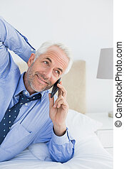 Relaxed mature businessman using mobile phone in bed -...