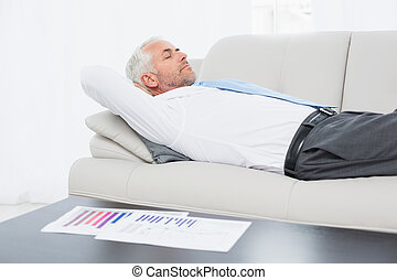 Businessman sleeping on sofa with g - Side view of a tired...