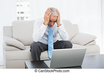 Worried businessman with head in hands in front of laptop at...