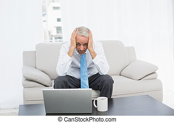 Portrait of a worried mature businessman with laptop at home...