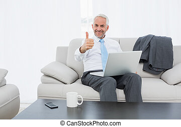 Businessman with laptop gesturing thumbs up at home