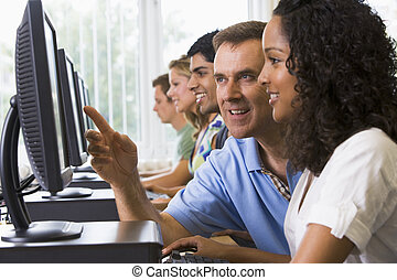 Four students sitting at computer terminals with teacher...