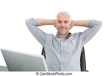 Businessman sitting with hands behind head with laptop -...