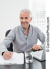 Smiling mature businessman writing notes while using laptop...