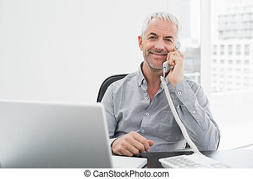Smiling businessman on call in front of laptop at office...