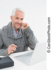 Portrait of a smiling mature man with laptop at desk against...