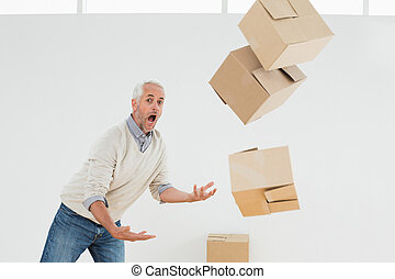 Side view of a mature man with falling boxes