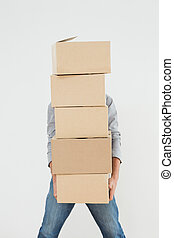 Obscured man carrying boxes against white background