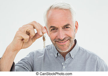 Close-up portrait of a smiling mature man holding house keys...