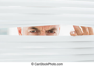 Close-up of a mature businessman peeking through blinds -...