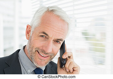 Close-up of smiling mature businessman using cellphone -...
