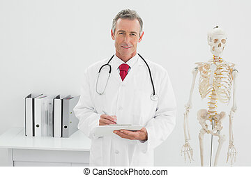 Confident male doctor writing a report at office - Portrait...