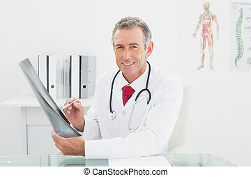 Smiling doctor with x-ray picture of lungs in office