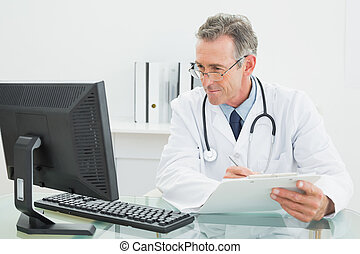 Concentrated male doctor with report looking at computer...