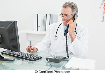 Doctor using computer and telephone - Smiling male doctor...
