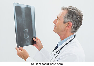 Concentrated male doctor looking at x-ray