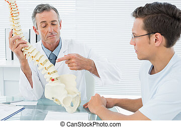 Doctor explaining spine to patient in office - Male doctor...