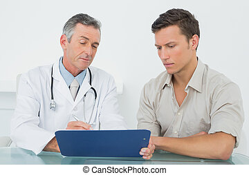 Doctor discussing reports with pati - Male doctor discussing...