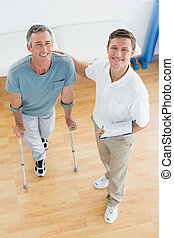 Therapist and disabled patient with reports in gym hospital