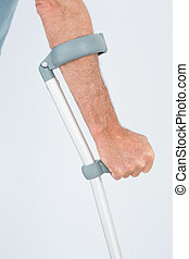 Close-up mid section of a man with crutch against white...