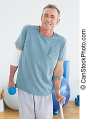 Smiling mature man with crutch and dumbbell - Portrait of a...