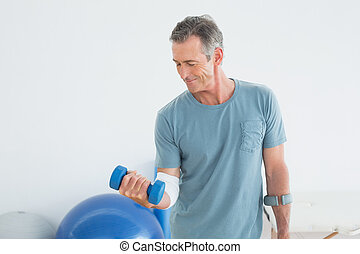 Smiling mature man with crutch and dumbbell at the gym...