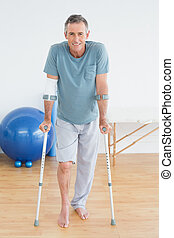 Smiling mature man with crutches at gym hospital - Full...