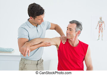 Physiotherapist massaging mature mans arm - Male...