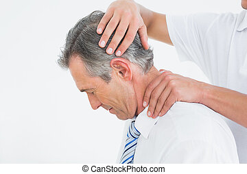 Chiropractor doing neck adjustment - Side view of a...