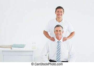 Male chiropractor and well dressed mature patient - Portrait...