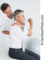 Male chiropractor examining mature man - Side view of a male...