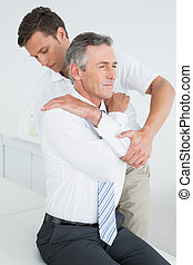 <ale chiropractor examining mature man - Side view of a...