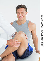 Portrait of a smiling young man getting his leg examined