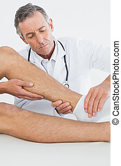 Close-up of a man getting his ankle examined