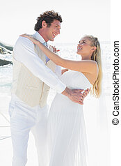Groom dipping his pretty new wife while dancing at the beach