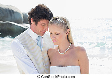 Peaceful bride and groom embracing at the beach