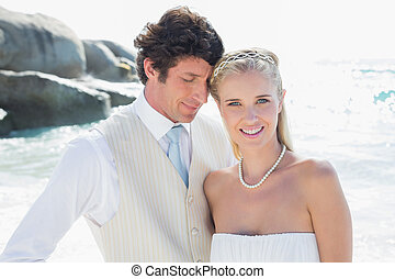 Happy bride and groom embracing at the beach