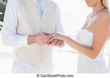 Man placing ring on smiling brides finger at the beach